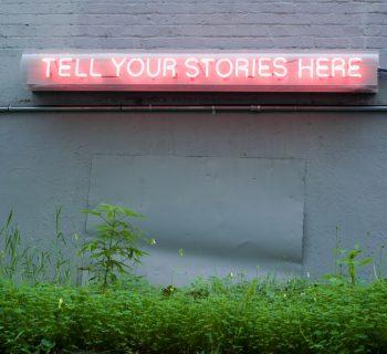 Tell Your Stories Here - Neon no exterior de um edifício